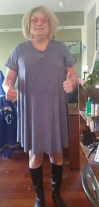 Paige is wearing a blue dress and long black boots with pink glasses both thumbs up in the air and a huge smile