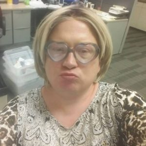Paige is weraring a leopard print top and her heart glasses and attempting to display a pouty lip smile.