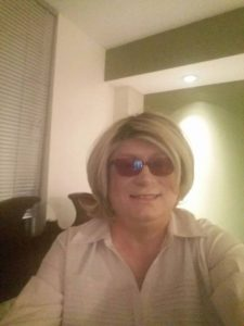 Paige is wearing a blonde wig and purple glasses with a huge grin.
